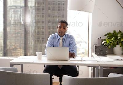 Portrait Of Male Financial Advisor In Modern Office Sitting At Desk Working On Laptop