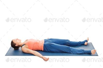 Women relaxes in yoga asana Savasana