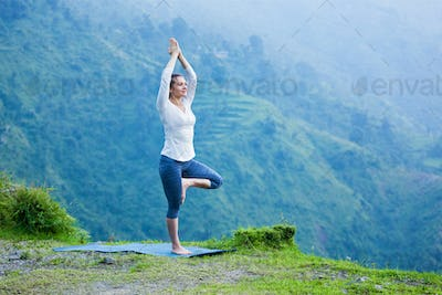 Woman in yoga asana Vrikshasana tree pose outdoors