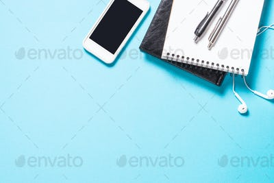 Notebook smartphone and pen on blue background