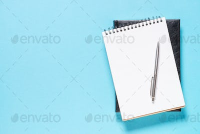 Notebook and pen on blue background