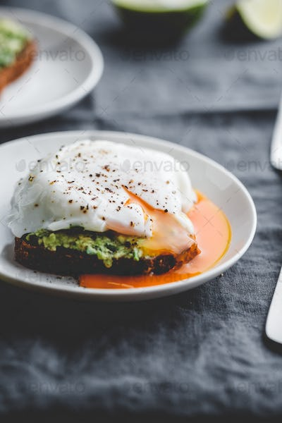 Avocado sandwich with rye bread and a poached egg