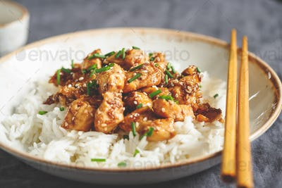 Sesame chicken pieces with rice on a ceramic plate. Chinese traditional dish.