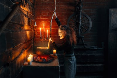Scary witch cooking soup and reads spell