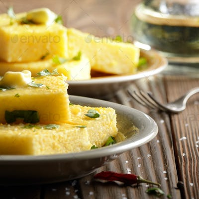 Polenta with butter and greens on clay dish on wooden rustic tab