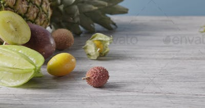 Panoramic slow motion of tropic fruits - pineapple, coconut, pitahaya on a wooden table on a blue
