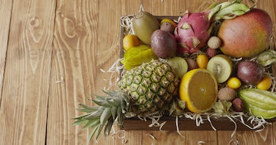 Panoramic video top view on a box with variety fresh natural organic exotic fruits on a wooden