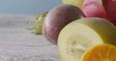 Close-up dolly slow motion of passion fruit, carambola, litchi on a wooden background. Concept of