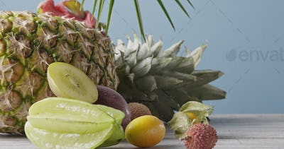 Freshly picked natural ripe exotic fruits with ripe pineapple on a wooden gray table on a blue