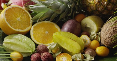 Assorted tropical fruits - halves of orange, pineapple, carambola, coconut and lichi with watering