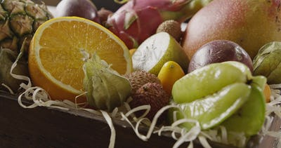 Close up view on a wooden box with fresh exotic fruits. Panoramic motion, 4K UHD video, 3840, 2160p