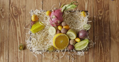 Top view woman's hand puts natural organic mango, pineapple, kiwi in a the box with variety