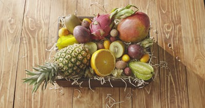 The motion of sunlight above the wooden box with fresh natural organic tropical fruits on a wooden