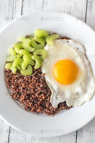 Portion of red quinoa with fried egg and celery