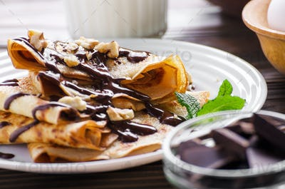 French crepes with chocolate sauce walnuts eggs and flour on woo