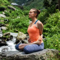 Young fit woman doing yoga oudoors at waterfall