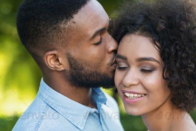 Loving black man kissing his girlfriend while walking