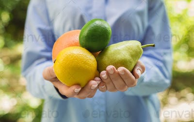 Woman holding various fresh fruits in hands outdoors