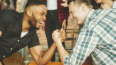 Cheerful friends having fun arm wrestling