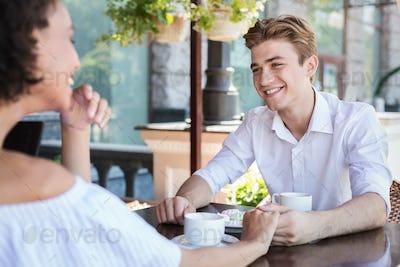 Happy interracial couple flirting at summer terrace