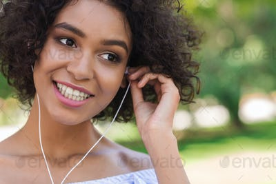Smiling black woman with earphones listening to music