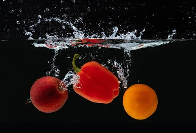 Fresh apple, orange and pepper water splash on black
