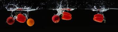 Fresh apple, orange and pepper water splash on black