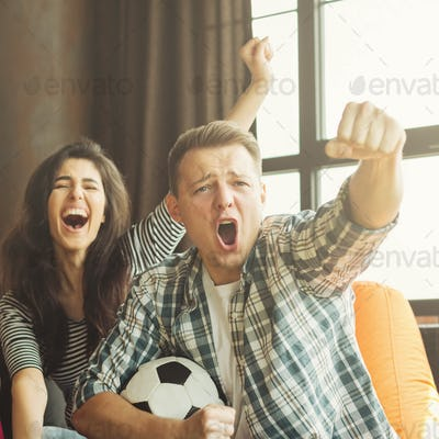 Man and wooman football fans watching game
