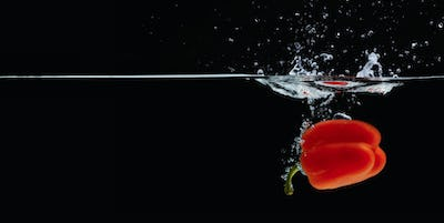 Colored orange paprika in water splashes on black background