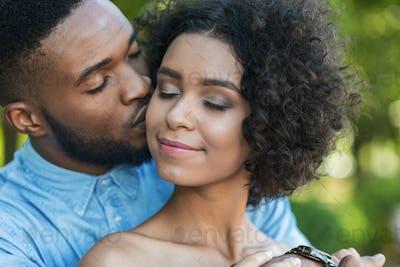 Handsome man kissing tenderly his girlfriend in cheek