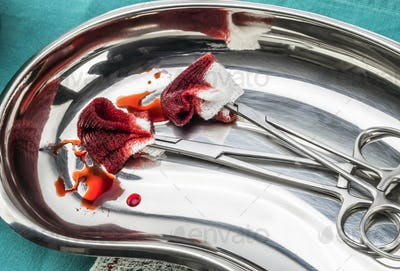 Scissors surgical with torundas soaked with blood on a tray metal in an operating theater