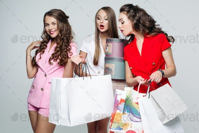 Fashionable girlfriends after shopping surprised looking inside bags