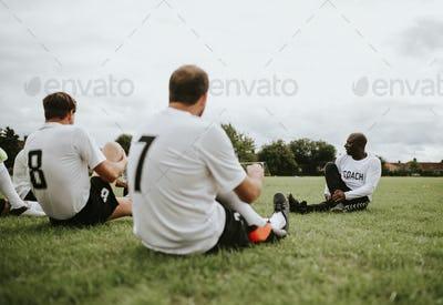 Male football players stretching together