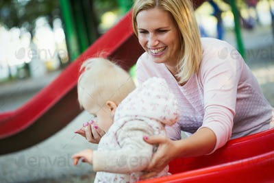 Little girl and her beautiful young mother playing on the playground