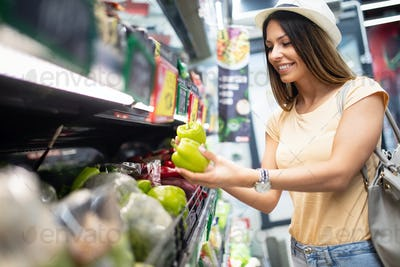 Smiling happy woman doing shopping in supermarket