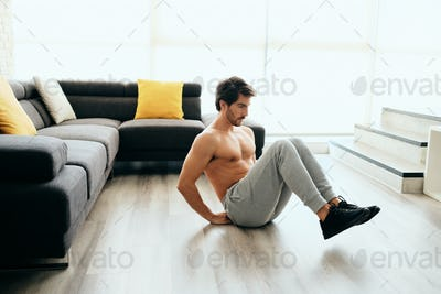 Young Man Working Out At Home For Healthy Lifestyle And Fitness