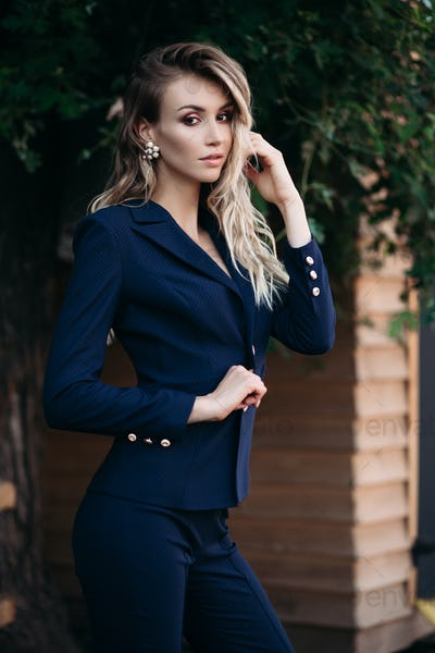Elegant blonde woman in dark blue suit with gold buttons