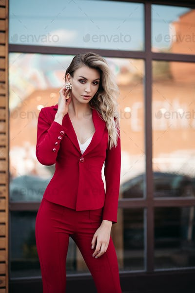 Elegant blonde woman in dark red suit with gold buttons