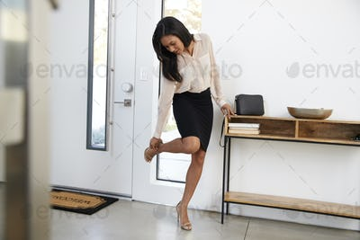 Businesswoman Wearing Suit Returning Home From Work And Taking Off Shoes