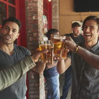 Group Of Male Friends Meeting In Sports Bar Making Toast Together