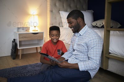 Father With Son Sitting In Bedroom Playing Game On Digital Tablet Together
