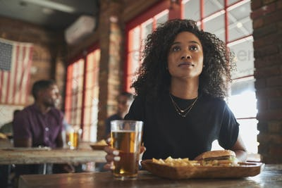 Woman Watching Game On Screen In Sports Bar Eating Burger And Fries