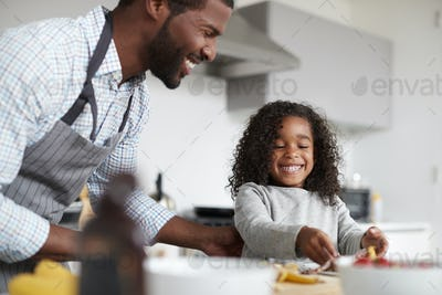 Father And Daughter In Kitchen At Home Making Pancakes Together