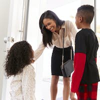 Children Greeting And Hugging Working Businesswoman Mother As She Returns Home From Work