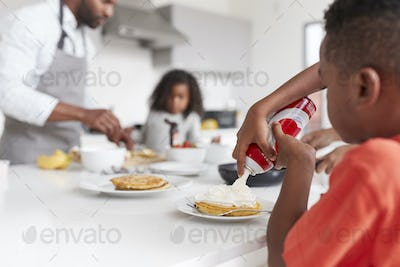 Boy Adding Cream To Pancakes As Family Enjoy Breakfast In Kitchen At Home Together