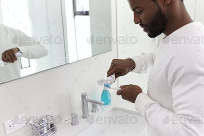 Close Up Of Man Squeezing Toothpaste Onto Toothbrush In Bathroom
