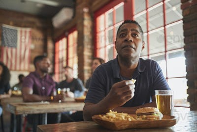 Man Watching Game On Screen In Sports Bar Eating Burger And Fries