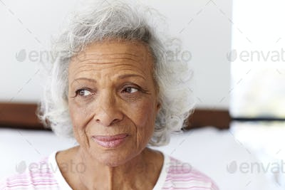 Depressed Woman Looking Unhappy Sitting On Side Of Bed At Home