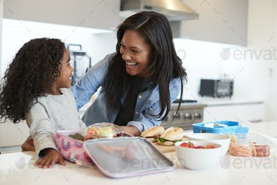 Daughter In Kitchen At Home Helping Mother To Make Healthy Packed Lunch