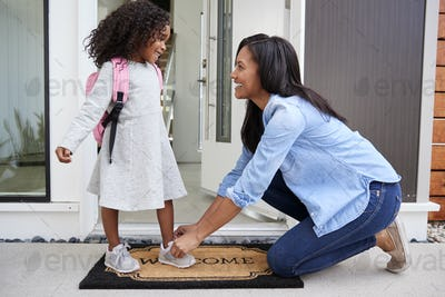 Mother Tying Daughters Shoelaces As She Leaves For School